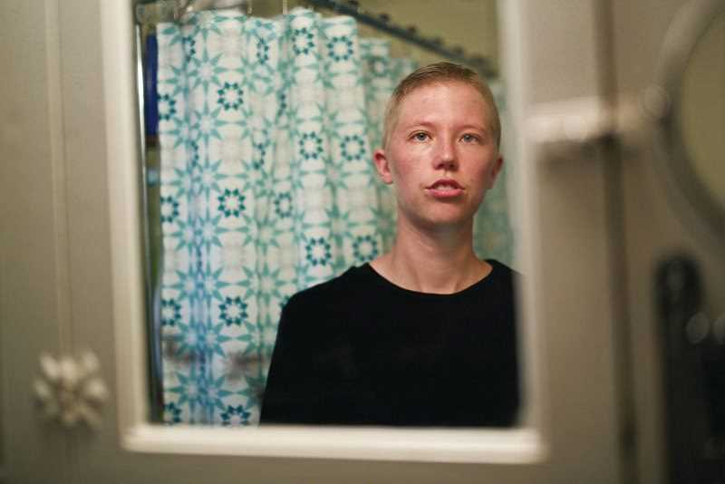 TIMES FILE PHOTO - Leo Soell looks in the mirror in 2015. Soell, who is transgender, settled a complaint with the Gresham-Barlow School District. Soell, a fifth-grade teacher in the district, said that teachers and administrators harassed them after Soell came out as transgender.
