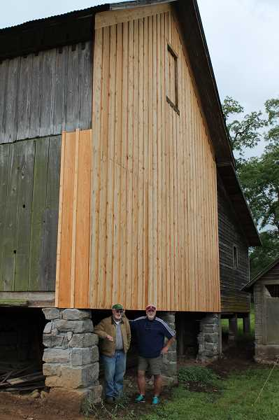 REVIEW PHOTO: ANTHONY MACUK - Rick Cook and his brother, Steve Cook, stand in front of the new foundation for the Shipley-Cook farms historic barn, built in 1860.