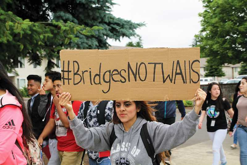 INDEPENDENT PHOTO: TYLER FRANCKE - A student participating in Wednesday morning's walkout holds a sign that says '#BridgesNotWalls.'