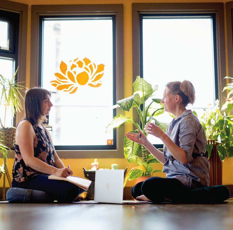 TRIBUNE PHOTO: JONATHAN HOUSE - Yoga therapist Kate Holly (L) consults with her business coach Ashley Dahl about how bring her best self to her business Yoga Refuge. Business coaching is a booming business and is spreading from the C-Suite to the gig economy.