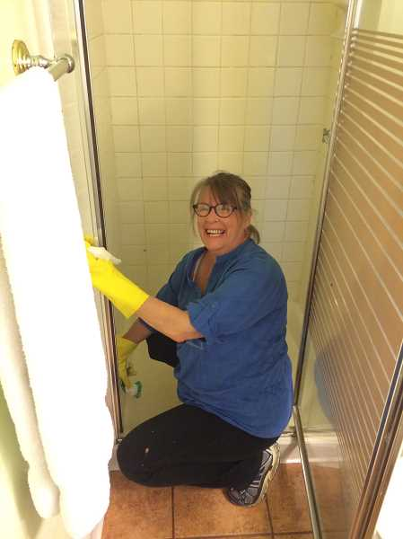 SUBMITTED PHOTO: ANDY MCCANDLESS  - Volunteer Cindy Roberts cleans the shower of a mother and cancer patient, part of the services through Michelle's Love.