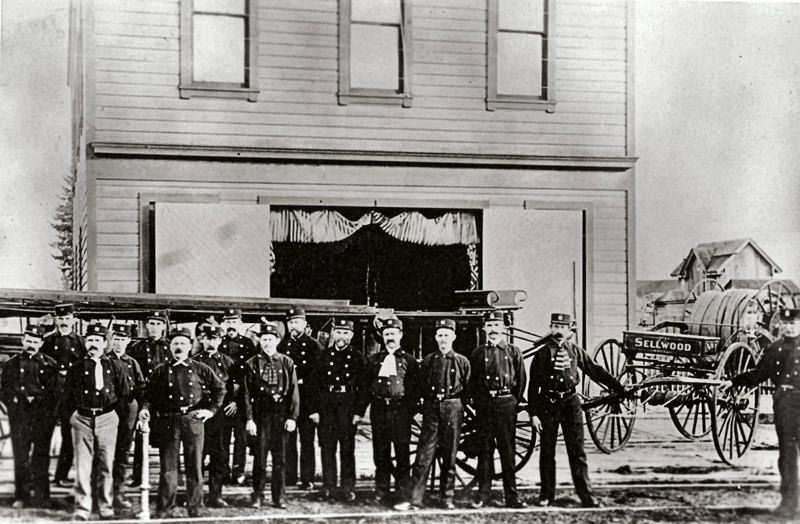 PHOTO COURTESY OF THE SMILE HISTORY COMMITTEE - Men of the Sellwood Volunteer Fire Department, here preparing for inspection. Fire Hose? Check. Fire Ladder? Check. Firefighting neckties? Mustaches groomed and waxed? Check! Horses ready to go? ...Wait a minute! We dont have any horses. Were real men, and well push this ladder truck all the way down 13th Avenue by ourselves! (This early firehouse at 13th and S.E. Tenino is now the site of SMILE Station.)
