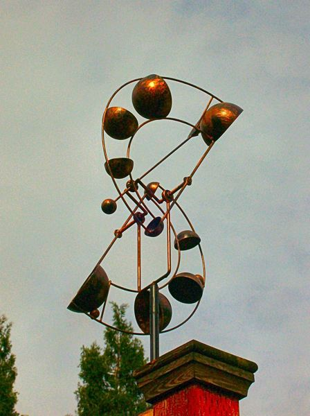 RITA A. LEONARD - This wind spinner, created with rotating metal bowls, changes its apparent shape with the direction of the wind.
