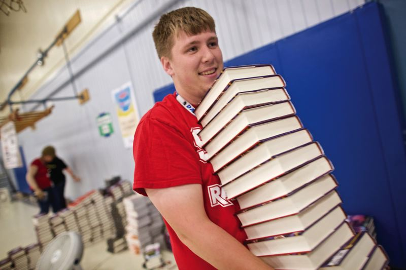 TIMES PHOTO: JAIME VALDEZ - Ian Hand of Oregon City moves a stack of books during a First Book event at William Walker Elementary School.