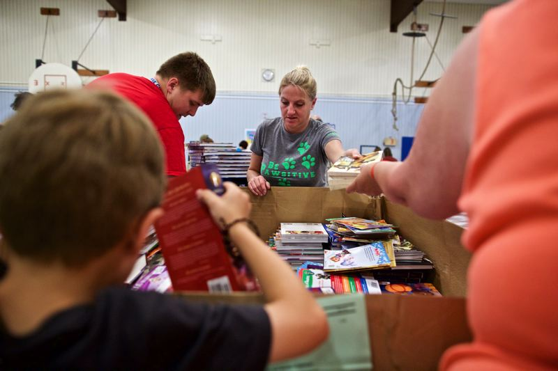 TIMES PHOTO: JAIME VALDEZ - Debbie Stensrud, middle, a special education assistant at Greenway Elementary School, unpacks books during a First Book event at William Walker Elementary School.