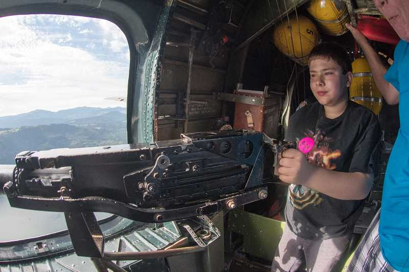 OUTLOOK PHOTO: JOSH KULLA - Mason Rolofson, 11, of Corbett, takes his turn behind one of the .50 caliber Browning machine guns in the waist position onboard the Witchcraft as it flies over the Columbia River.