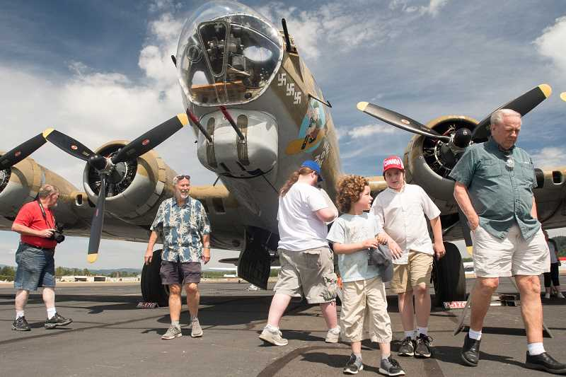 OUTLOOK PHOTO: JOSH KULLA - Aircraft enthusiasts photograph and enjoy the B-17G Nine-O-Nine at Troutdale Airport Wednesday, part of the Collings Foundation Wings of Freedom tour.