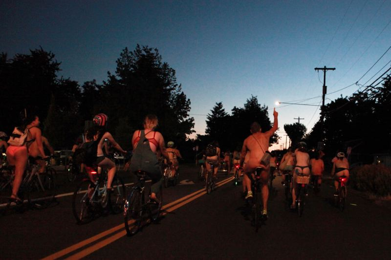 COURTESY PHOTO: SHIRLEY CHAN/OPB - World Naked Bike Ride participants ride into the night on Woodstock Boulevard with high energy Saturday, June 25.