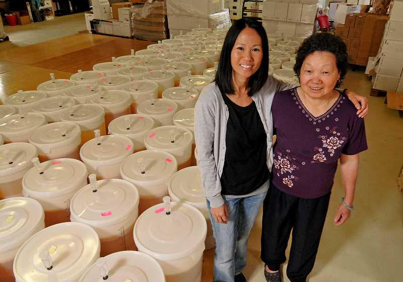 SPOKESMAN PHOTO: VERN UYETAKE - Michelle Ly, left, and her mother Kim Trinh came to Wilsonville as refugees with their family in 1979. Their family has brewed baijiu for generations.