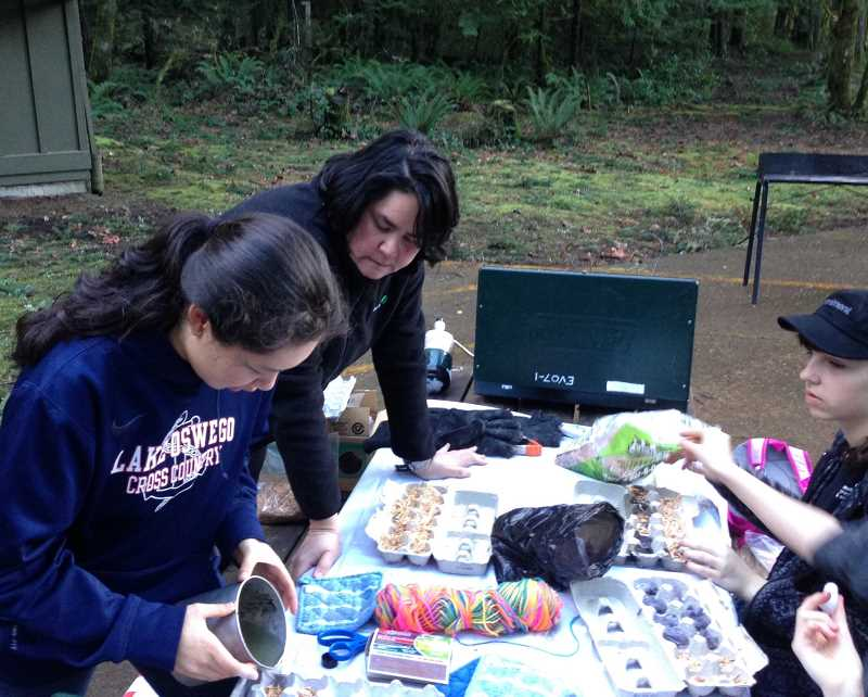 SUBMITTED PHOTO - Crystal Shum works with a couple of my girls to make firestarters at the Mountaindale Outdoor Program Center in North Plains. Shum recently was awarded the Girl Scout Honor Pin, one of the organization's highest awards for adults.