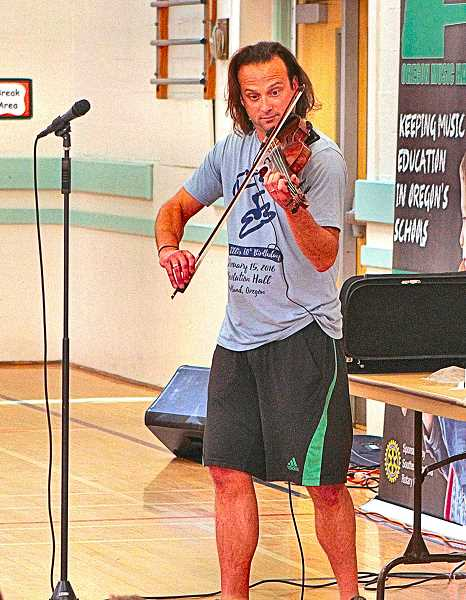 DAVID F. ASHTON - Rock violinist Aaron Meyer begins his June 1 concert at Llewellyn Elementary School, on S.E. 14th in Westmoreland.