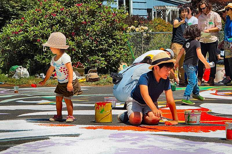 DAVID F. ASHTON - Two of the seven kids visiting from Japan get a taste of Portland culture - by helping paint a street mural in the Brentwood-Darlington neighborhood.
