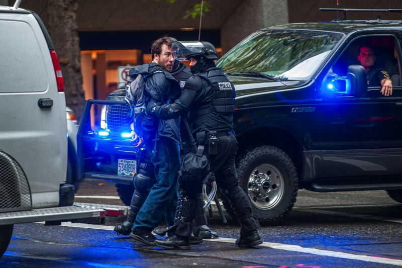 TRIBUNE PHOTO: DIEGO DIAZ - Portland police in riot gear took a man who waved a gun into custody Thursday evening during a rally and march organized by Don't Shoot Portland.