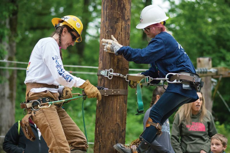 COURTESY: BONNEVILLE POWER ADMINISTRATION - A sexist work environment can easily become unsafe, says Cristi Sawtell, here demonstrating climbing technique to a novice at a Women in Trades Fair held last year.