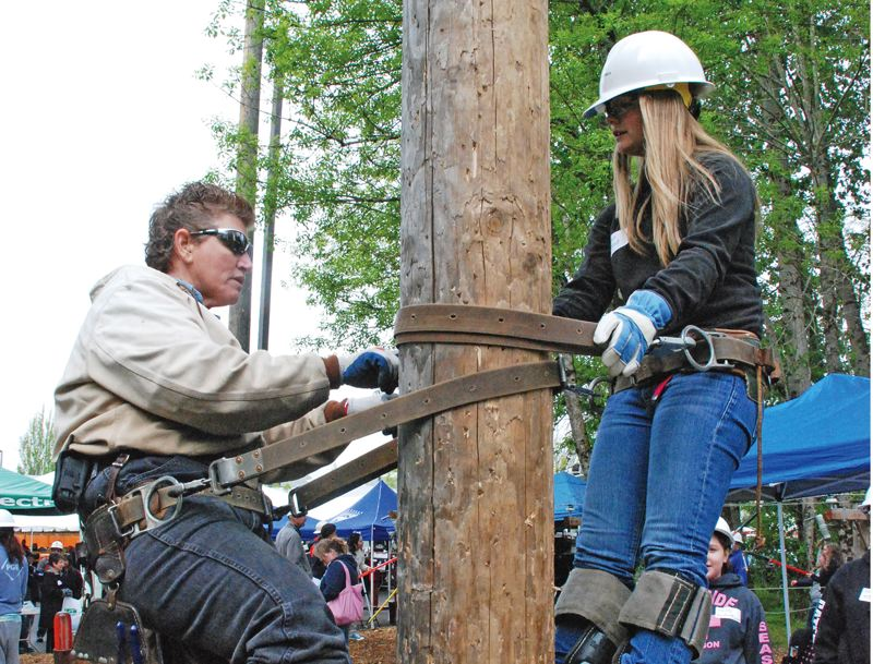 COURTESY: OREGON TRADESWOMEN, INC. - Line worker Suni Miani says she was subjected to intense harrasment during her days in Oregon. Here Miani, left, shows a middle schooler how to safely climb a utility pole.