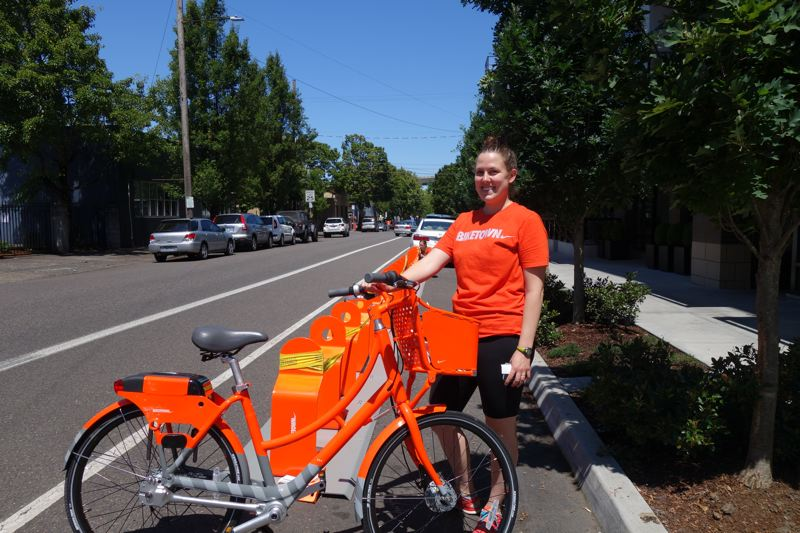 TRIBUNE PHOTO: JOSEPH GALLIVAN - Biketown installer Emily Leuning preparing bike racks on Northwest 19th Avenue. The bikeshare bikes carry their electronics with them and lock to simple steel posts.