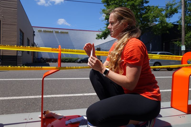 TRIBUNE PHOTO: JOSEPH GALLIVAN - Alena Almquist-Heater last week preparing bike racks on Northwest 19th Avenue. Becasue they are run by the Portland Bureau of Transportation the bike racks often occupy the roadway, taking up two parking spaces.