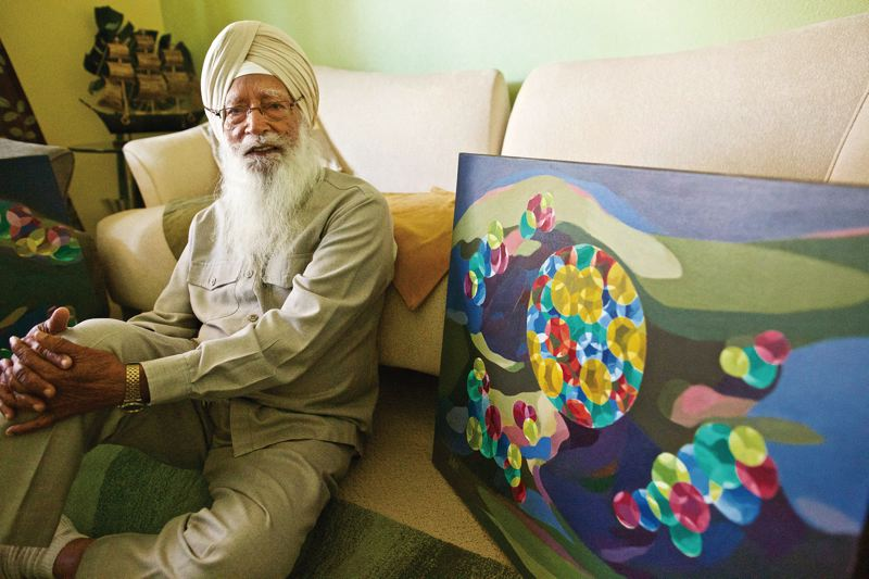 TIMES PHOTO: JAIME VALDEZ - Artist Ram Singh Bawa sits in his living room with a painting that will be featured at the Beaverton Night Market this month.