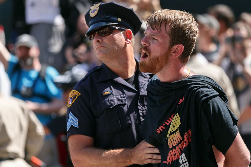 TRIBUNE PHOTO: JOHN RUDOFF - A protester has just been arrested after a flag-burning protest and melee at the entrance to the Quicken Loans Arena.
