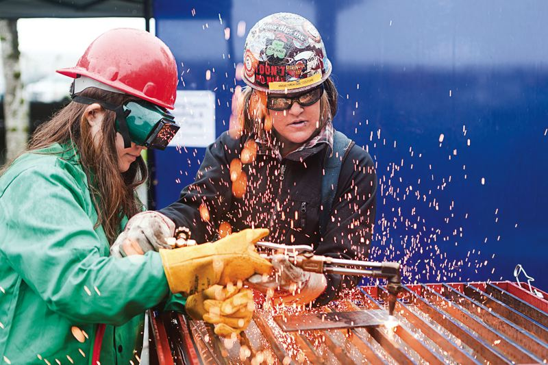 COURTESY PHOTO: JIM GOLDEN - Journey-level ironworker Angela Couture teaches a middle-schooler how to use a cutting torch.