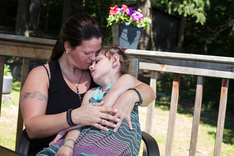 TRIBUNE PHOTO: JONATHAN HOUSE - Cyndy cradles her daughter Blue during a visit to Cyndy's mother-in-law's house. Blue enjoys the trips because her grandmother has a pool that she can float in.
