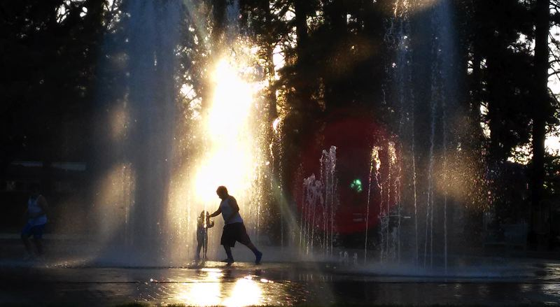TIMES PHOTO: MILES VANCE - Children splash and play in the fountains at Beaverton City Park as the sun sets at 8 p.m. Sunday.