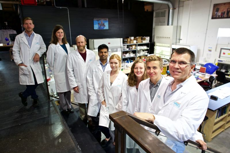 TIMES PHOTO: JAIME VALDEZ - Charles Keller,right, founder of the Children's Cancer Therapy Development Institute, stands with his staff by the lab in Old Town Beaverton.