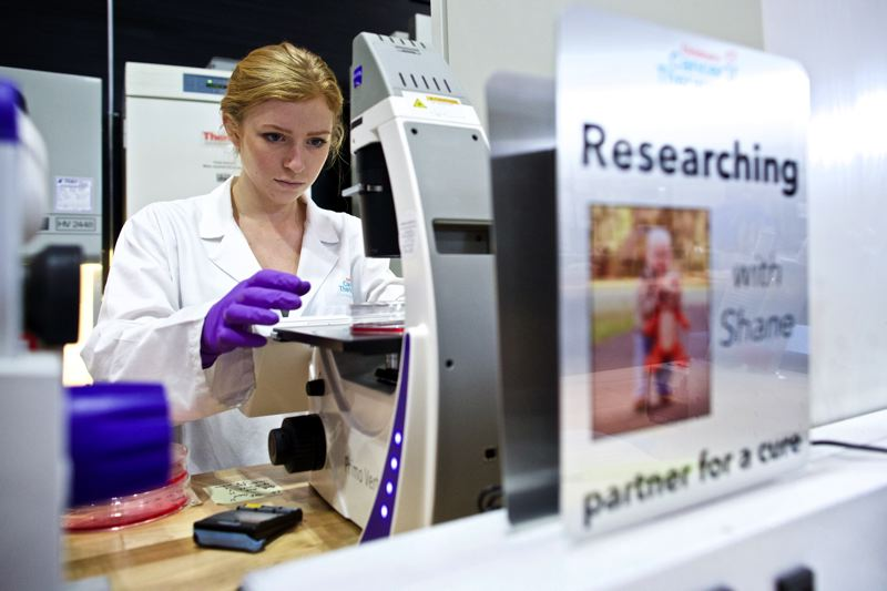 TIMES PHOTO: JAIME VALDEZ - Morgann Turkot, a biomedical engineering fellow, looks at cancers cells under a microscope at Childrens Cancer Therapy Development Institute.