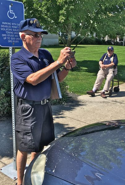 TRIBUNE PHOTO: DEAN BAKER - Len Stanley photographs a violator to write a ticket while Walter Hull, right, looks on.