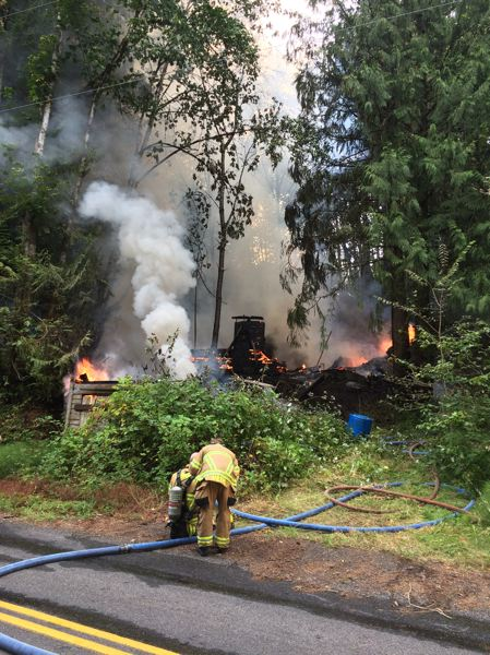 SCAPPOOSE FIRE DISTRICT PHOTO - Fire crews extinguish flames on an abandoned house on EJ Smith Road in Scappoose Sunday morning, Aug. 7.
