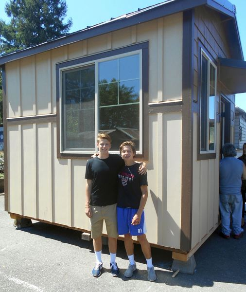 FOR THE TIMES: PHIL FAVORITE - Oregon Episcopal School students Henry Morissette (left) and Jack Morisette pose in front of the tiny house they built and delivered to Dignity Village in Portland on Friday.