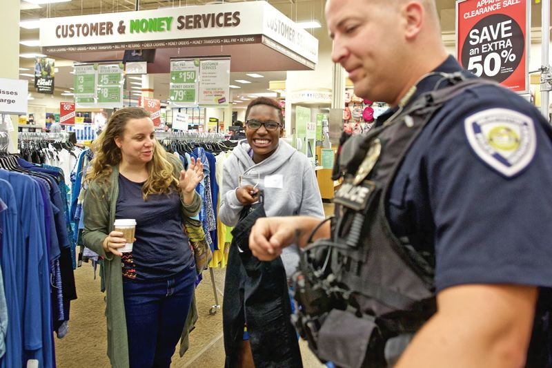 TIMES PHOTO: JAIME VALDEZ - Lisa Ishmwe,13, middle, smiles after picking a pair of jeans she would like to try on during a Shop with a Cop event with Beaverton Police Department Officer Jeff Gill and her family friend, Jina, at Fred Meyer in Beaverton. Tuesday was Ishmwe's second day in America.
