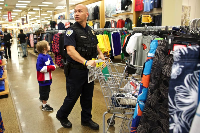 TIMES PHOTO: JAIME VALDEZ - Beaverton Police Department Officer Ryan Potter leads Luke, 8, to find another back to school item during a Shop with a Cop event at Beavertons Fred Meyer.