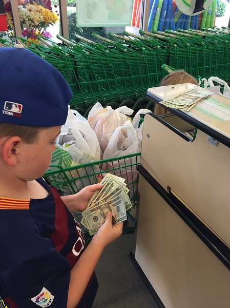 SUBMITTED PHOTO - Brayden counts some of his hard-earned money while shopping for welcome box supplies.