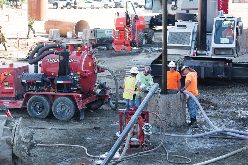 JONATHAN HOUSE - Contractors drill concrete pilings 80 feet deep into the ground, letting it set inside hollow steel frames. Theyre installing two to four concrete columns a day.