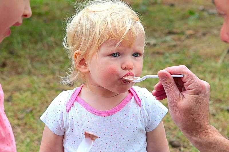 DAVID F. ASHTON - The little girl taking a big bite of ice cream, at the 2016 Sundae in the Park in Sellwood Park, is Margaret Anderson.