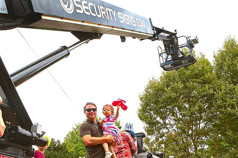 DAVID F. ASHTON - Jeff Buono holds Tessa, while exploring Security Signs truck at the Big Truck Day festivities in the Reed neighborhood.