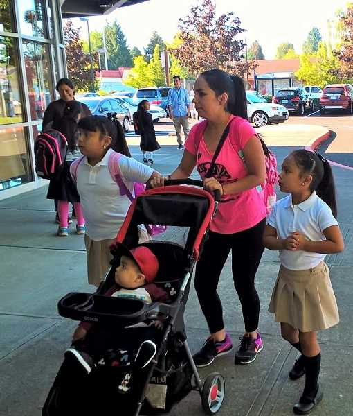 Melanie Vazquez Gonzalez (right) is entering second grade and her sister Aleida Vazquez Gonzalez (left) is entering third grade. They walked into the front doors at Cornelius Elementary with their mother and little brother.