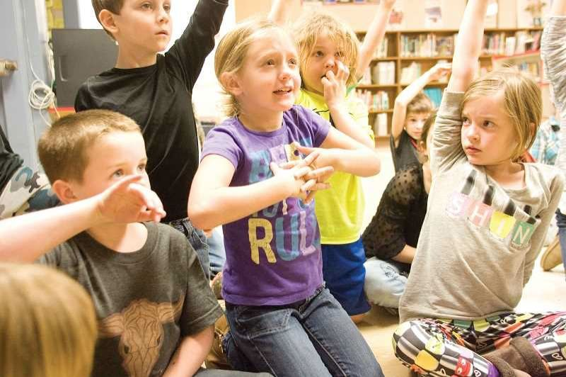 FILE PHOTO - Second graders raise their hands at a local school.