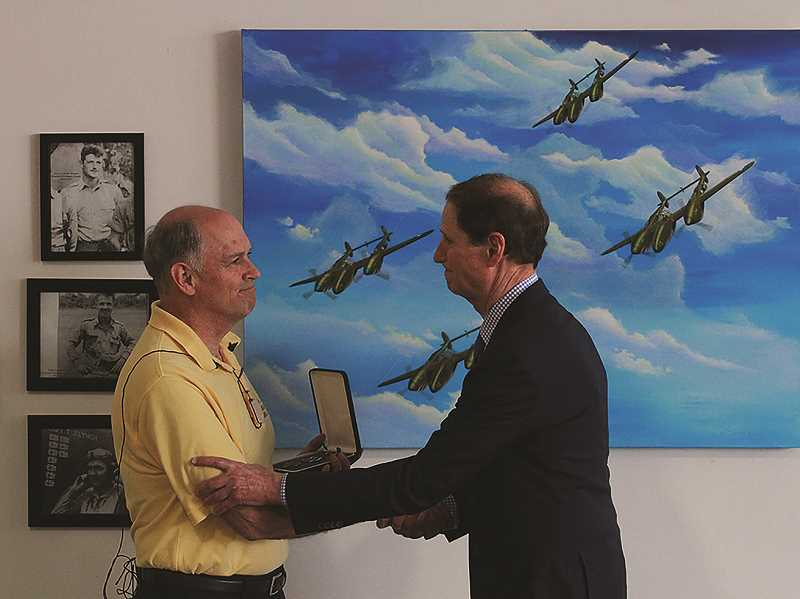 INDEPENDENT PHOTO: LARRY COONROD - John Mangas' nephew Gary Smith (left) accepts the Distinguished Flying Cross from Sen. Ron Wyden during a Sept. 4 ceremony at Lenhardt Airpark in Hubbard. The medal recognizes the bravery that cost Mangas his life on Jan. 8, 1943 while flying a P-38 fighter over Lae, New Guinea.
