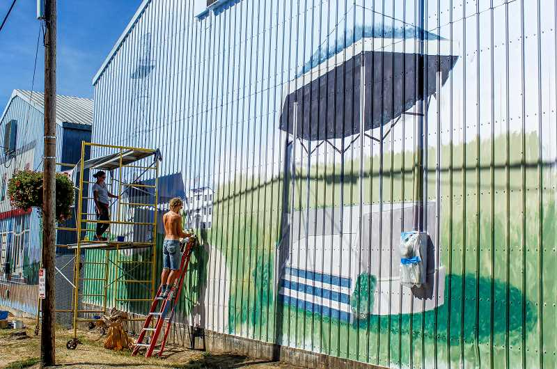HILLSBORO TRIBUNE PHOTO: TRAVIS LOOSE - Portland artists Allison McClay and James Nielson work on one of six large murals covering four warehouses on Northwest Commercial Street in downtown North Plains. The murals should be complete by the first week of October.