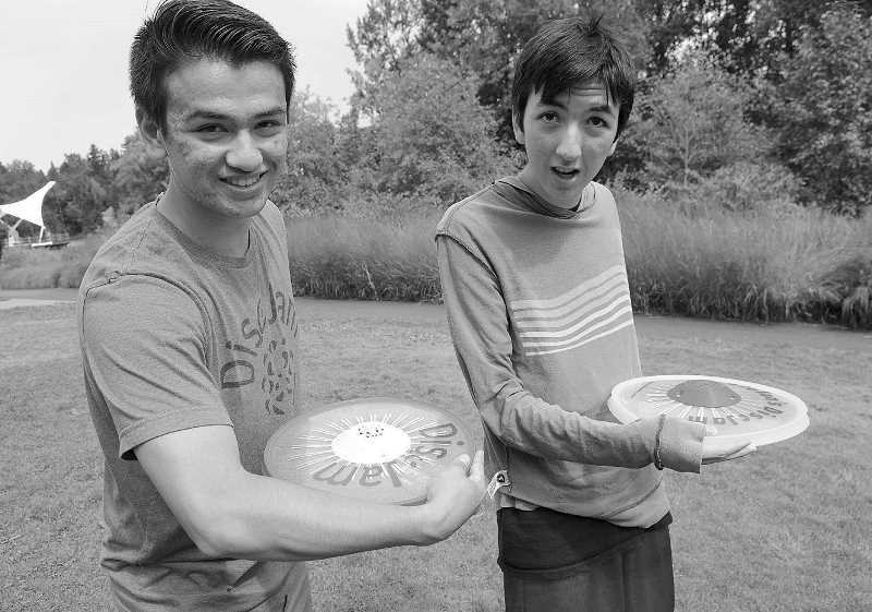 REVIEW PHOTO: VERN UYETAKE - Alex Dassise (left) and brother Stefan Seiji Dassise demonstrate one way to use DiscJam, which also can be used to complement speech therapy.