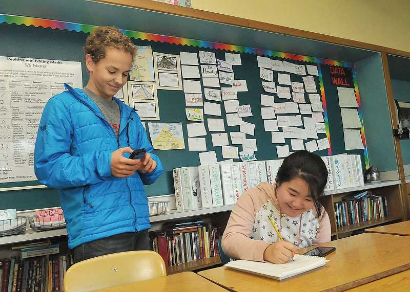 REVIEW FILE PHOTO: VERN UYETAKE - Seventh-graders Morne Wolmarans (left) and Amy Park discuss details concerning the LOJ Hunger Fighters Clubs campaign at a December 2014 meeting.
