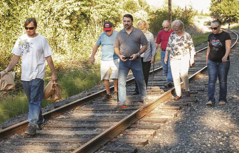 HILLSBORO TRIBUNE PHOTOS: TRAVIS LOOSE - David Swearingin (center) walks with his wife Niki (right) and members of his congregation in search of homeless campers in need of food and supplies on Monday, Sept. 12.