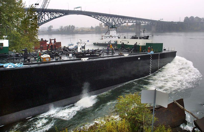 PAMPLIN MEDIA GROUP:  - A new barge from Zidell Marine Corp hits the water while tugs wait to push it into place against the Zidell dock in October 15, 2003. Zidell is getting out of the barge building business and plans to redevelop more of its 33 acre site.
