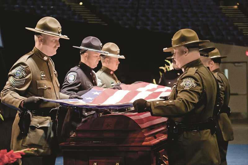 COURTESY DARCI VANDENHOEK - Officers and sheriffs deputies fold an American flag at thefuneral of Oregon City reserve police officer Robert Libke in 2014. Hillsboro Police are working with the Oregon Fallen Badge Foundation about how to handle line-of-duty officer deaths.