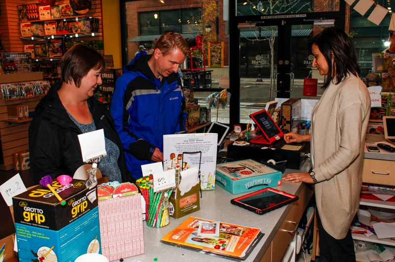 HILLSBORO TRIBUNE PHOTO: TRAVIS LOOSE - Buyuksahin helps Beaverton residents Julie and James Duffin (L-R) buy their daughter a perfume-making kit for her birthday Friday, Sept. 23. 