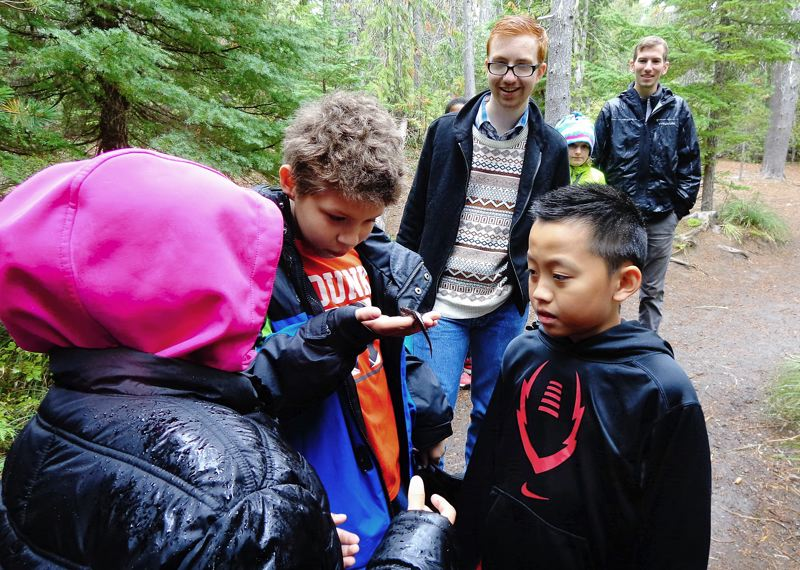 SUBMITTED PHOTO - Three Passport Oregon explorers, Ines (left to right), Kris and Erik, examine a salamander during a hike in the Mount Hood National Forest while Alex Hatch and Kevin Frazier look on.