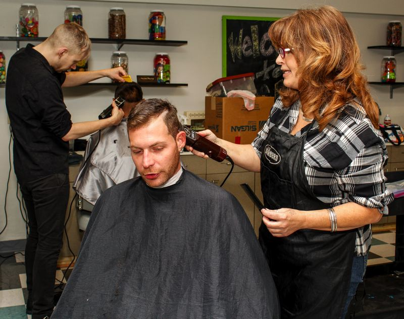 HILLSBORO TRIBUNE PHOTO: TRAVIS LOOSE - During the event, more than 100 haircuts were provided by folks like stylist Cheryl Van Dyke (R),  who said it was her sixth time volunteering for Project Homeless Connect.'I've been homeless,' Van Dyke said while cutting Nicholas Albers hair. 'I feel very fortunate to be on this side of the chair.' For Albers, a concessions cook at the Moda Center, getting a haircut helps wil self-confidence, he said. 'You look good, you feel good, y'know?'