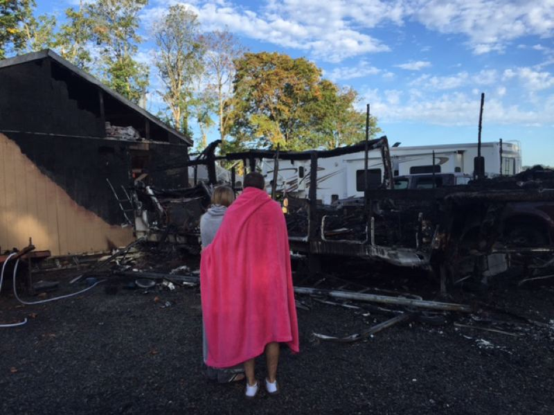 PHOTO COURTESY OF TROY HANNEMANN - Taylor Krumm and Jordan McCoy look over the burnt remains of the fifth-wheel trailer. The couple had stored personal belongings in the trailer while moving out of an apartment before the fire broke out.